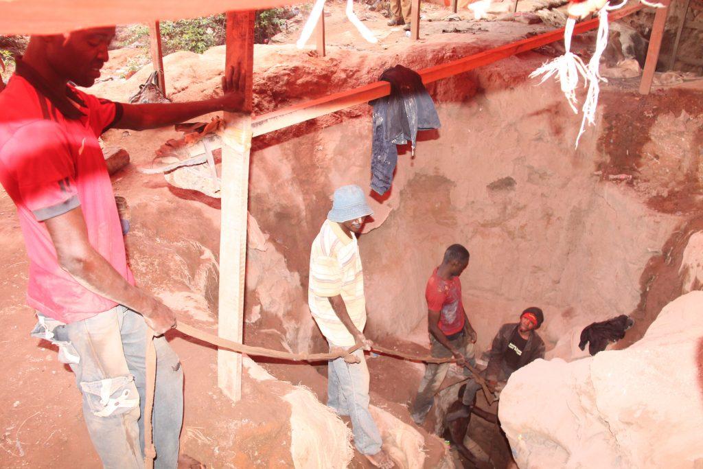 Trois mineurs artisanaux tirant un sac remplis de terre au Quartier Kasulo à Kolwezi.
