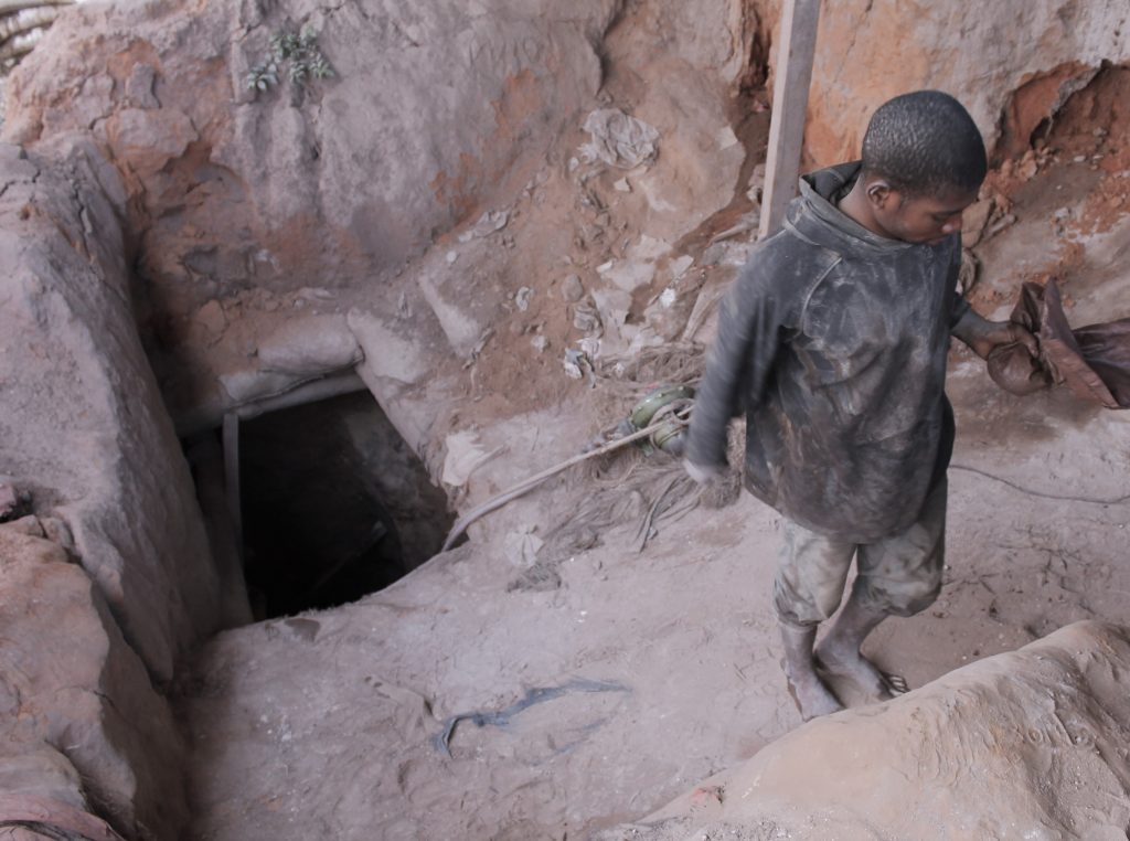 Un creuseur sortant de son puits des mines au Quartier Kasulo à Kolwezi