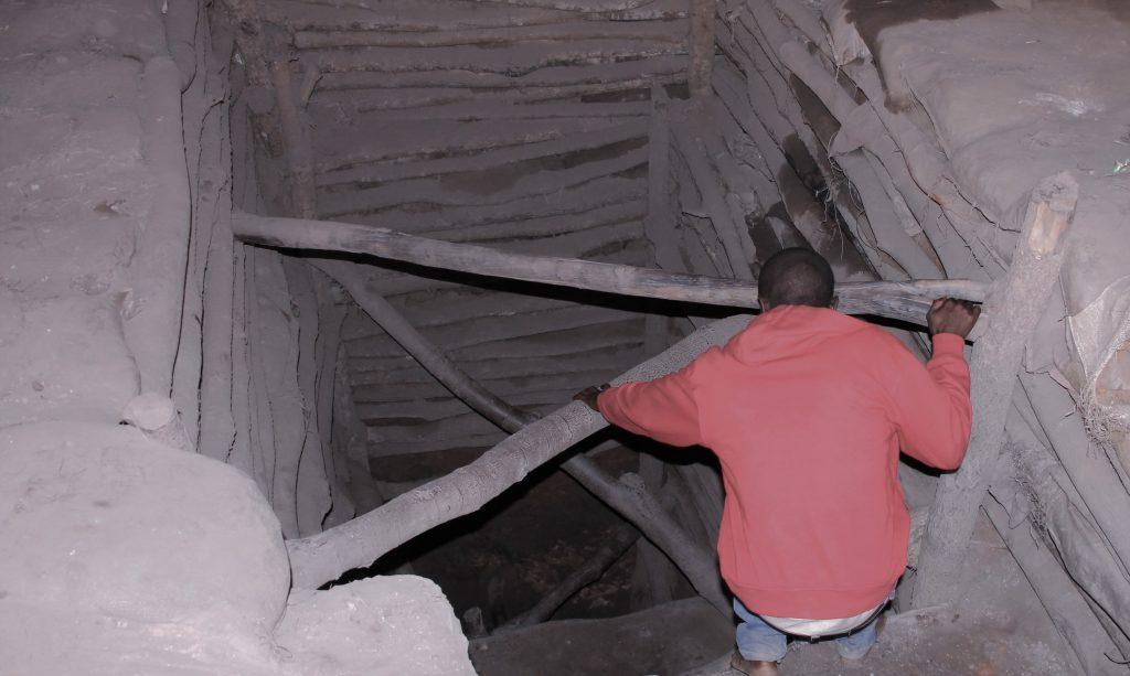 Un creuseur entre dans son puits des mines au Quartier Kasulo à Kolwezi