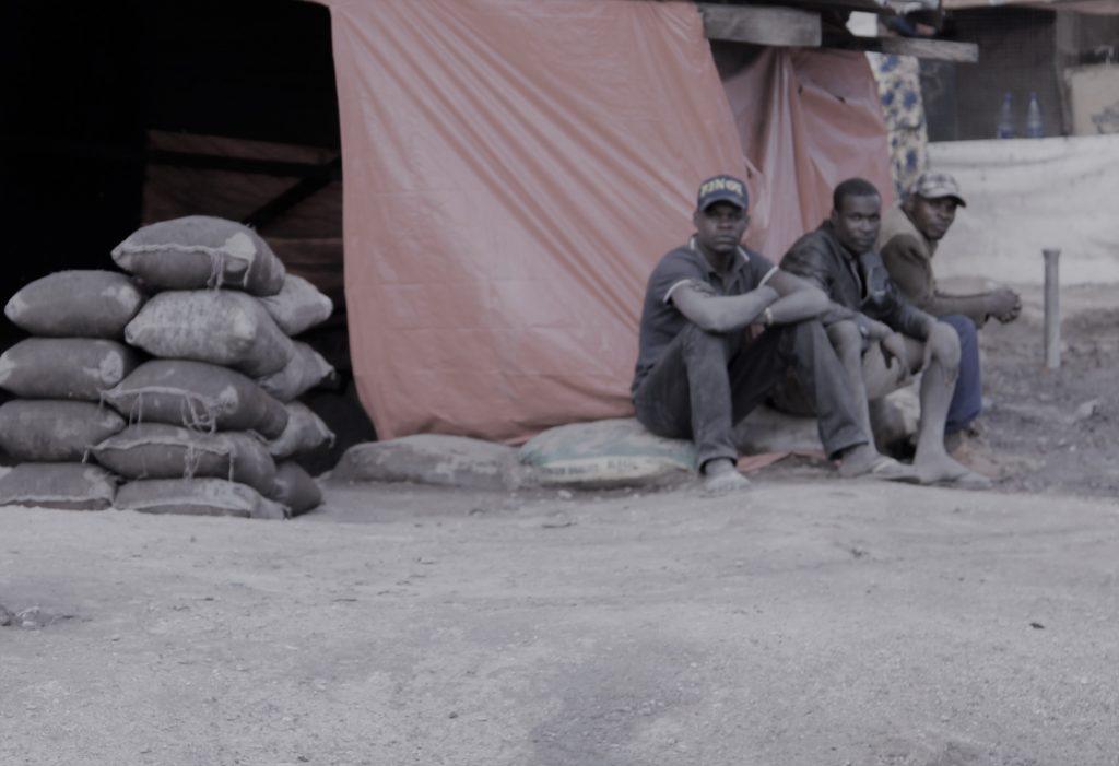 Trois creuseur devant leur tente en bâche à Kasulo à Kolwezi