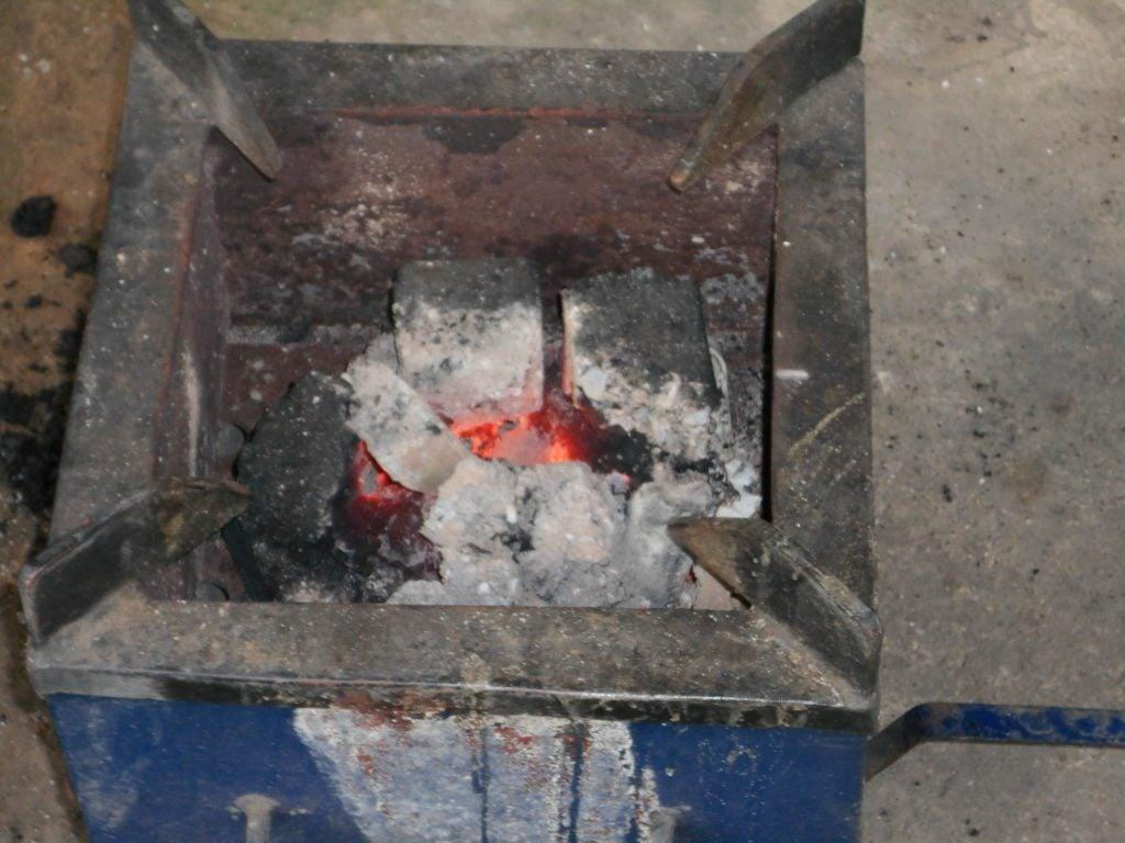 un brasereau contenant des morceaux de charbon écologiques chauds, prêts pour la cuisson des repas