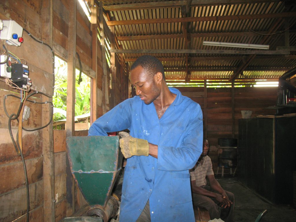 A l'unité de production, un agent de Kemit Ecology remue la matière première versée dans une des machines servant à la fabrication du charbon écologique