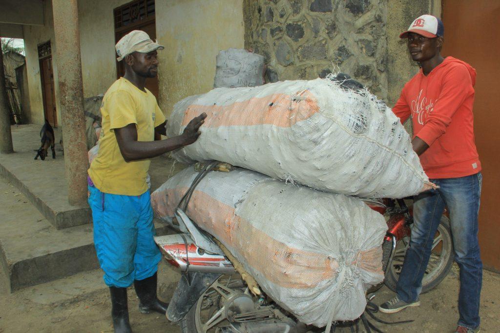 Des jeunes entrain de charger du charbon de bois avant de les transporter à un point de vente