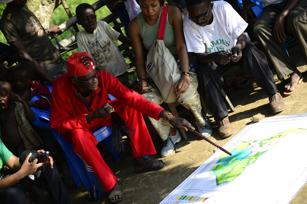 A community partnering with WWF in the DRC's Mai Ndombe region examines a map of their territory. (Photo: © WWF-US / Julie Pudlowski)