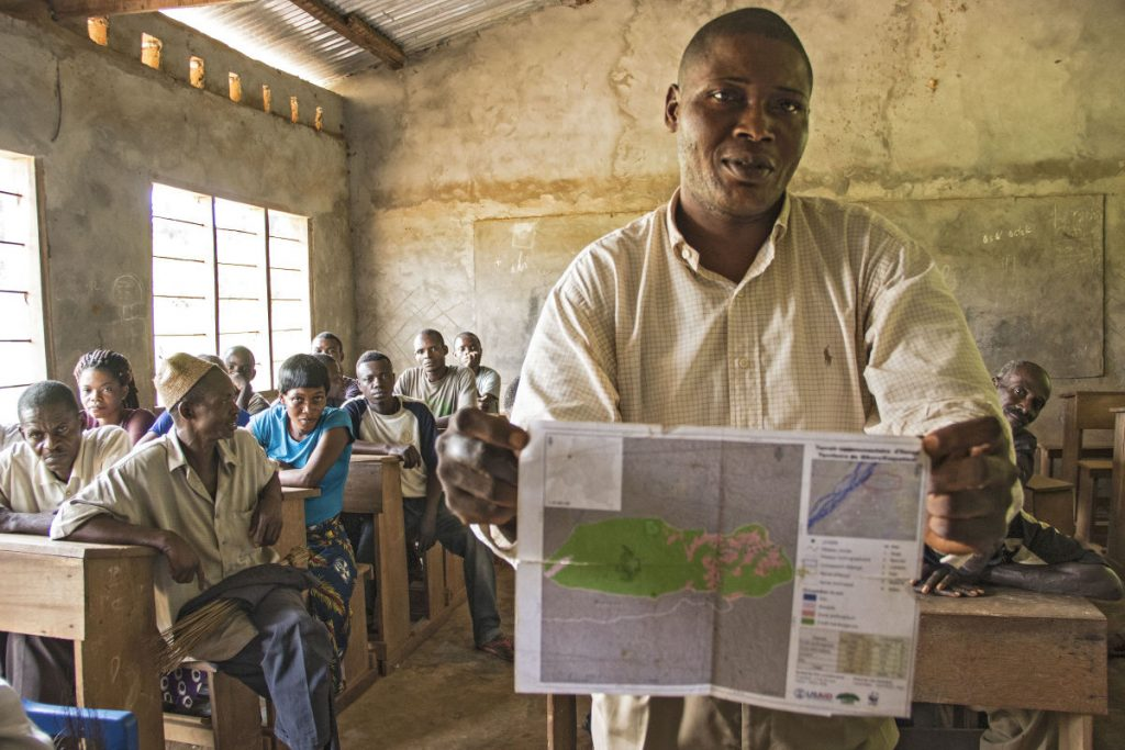 A man in Ilanga, DRC showcases a map his community created of their land and resources. The production of maps like these is an important part of the community forest concession process, as it requires community members to work together to determine boundaries and identify priority places to protect. (Photo by Molly Bergen/WCS, WWF, WRI)