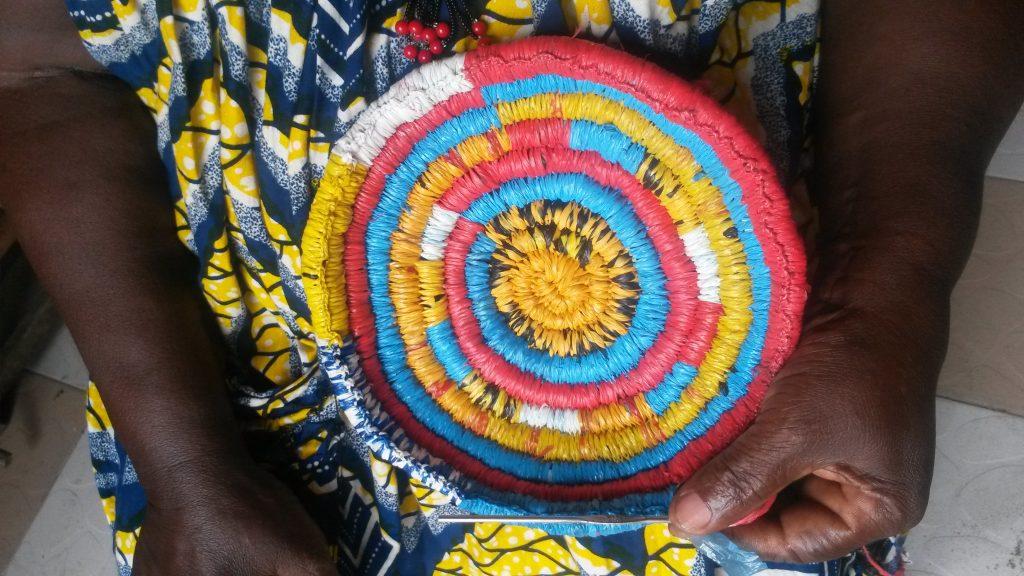 Aiguille à tricoter en main, Marie Mawabo confectionne un panier à base d'emballages plastiques recyclés